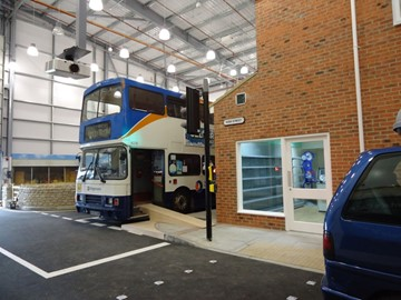A bus and a shopfront on a street at Gloucester Skillzone