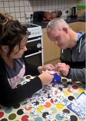 Support worker Caern, helps someone she supports with a puzzle