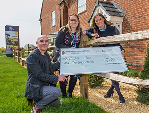 Brandon's fundraising team receiving a cheque from David Wilson Homes